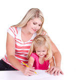 Mother helping daughter write alphabet Stock Image