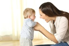 Mother helping her baby son in his first steps. Proud mother helping her baby son in his first steps at home Royalty Free Stock Images