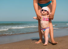 Mother Helping Her Baby Stand and Walk on the Beach Royalty Free Stock Photo