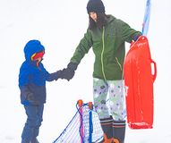 Mother helping her boy to ride the sled royalty free stock photography