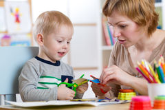 Mother helping her child to cut colored paper Royalty Free Stock Photography