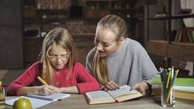 Mother helping her daughter with homework at home. Attentive young blonde mother helping her cute teenage girl with homework for junior high school at home stock video footage