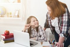 Mother helping her daughter with homework. Mother helping her daughter with her homework in the living room stock image
