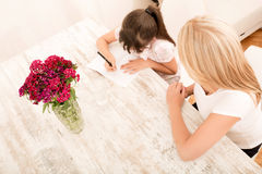 Mother helping her daughter with the homework Royalty Free Stock Photos