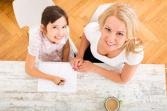 Mother helping her daughter with the homework Stock Images