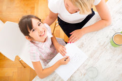 Mother helping her daughter with the homework Stock Photos