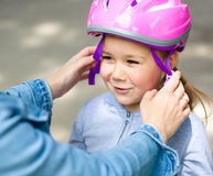 Mother is helping her daughter with safety helmet. Outdoors Royalty Free Stock Images