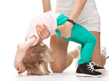 Mother helping her daughter to do gymnastics Royalty Free Stock Photo