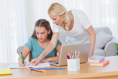 Mother helping her daughter to do her homework stock photos