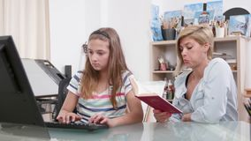 Mother helping her daughter to improve her typing skills stock footage