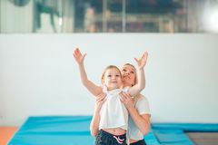 Mother helping daughter to play sports on gymnastic rings royalty free stock photos