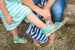 Mother helping her daughter to put on summer sandals Stock Photography