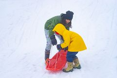 Mother helping her daughter to ride the sled royalty free stock photography