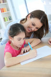 Mother helping her daughter to write Stock Photography