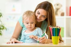 Mother helping her kid to make drawings Stock Images