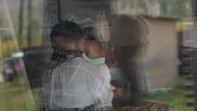 Mother Helping Her Little Daughter Get Dressed. View through the window stock footage