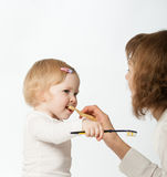 Mother helping her little dauther cleaning her teeth Stock Photos