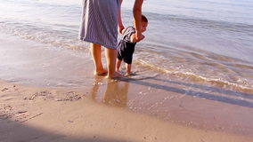 Mother helping her little son making first steps on the beach stock footage