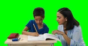 Mother helping her son while doing homework 4k. Mother helping her son while doing homework against green background 4k stock video footage