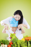 Mother helping her son make salad. Young Asian mother helping her son make a bowl of vegetables salad, shot with green screen background Royalty Free Stock Image