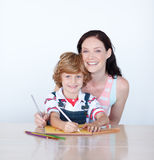 Mother helping her son to draw Royalty Free Stock Photos