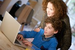 Mother helping her son use computer at home Royalty Free Stock Image