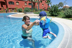Mother helping her young son to swim and jump in a sunny swimming pool stock photos