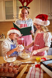 Mother helping kids at making Christmas cookies Stock Photos