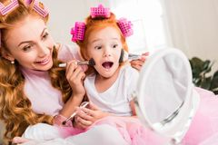 Mother and daughter doing makeup. Mother helping little excited daughter do makeup at home Stock Photos
