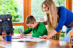 Mother helping with school homework assignment Stock Photography