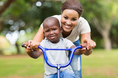 Mother helping son bicycle Royalty Free Stock Images