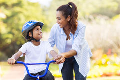Mother helping son bicycle Royalty Free Stock Photos