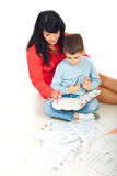 Mother helping son with homework. Mother helping her son with homework and making math exercises on floor in their home Royalty Free Stock Photo