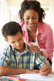 Mother Helping Son With Homework At Home Royalty Free Stock Photos