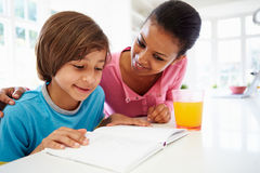 Mother Helping Son With Homework In Kitchen Stock Photo