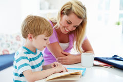 Mother Helping Son With Homework In Kitchen. Sitting At Table Looking At Textbook Stock Photos