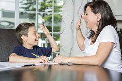 Mother Helping Son With Homework At Table Stock Photo