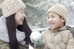 Mother helping son make snow ball Stock Image
