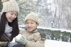 Mother helping son make snow ball Royalty Free Stock Images