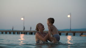 Mother helping son to jump in water stock video footage