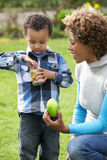 Mother Helping Son To Unwrap Chocolate Easter Egg. Smiling Royalty Free Stock Image