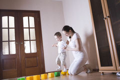 Mother Helping Son Walking On Cubes Stock Images