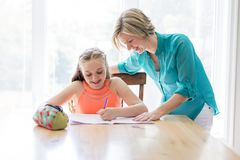 Mother helping teenaged girl with homework. A Mother helping teenaged girl with homework Stock Images