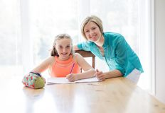 Mother helping teenaged girl with homework. A Mother helping teenaged girl with homework Stock Image