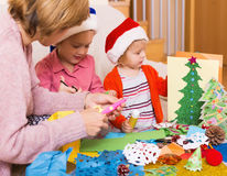 Mother helping  two girls to make decoration for Xmas Royalty Free Stock Photography