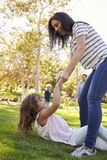Mother Helping Up Daughter During Family Soccer Game Royalty Free Stock Photo