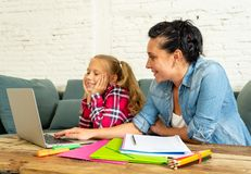Mother helping young girl doing homework with laptop and school books sitting on the sofa at home in parenting homework and stock photos
