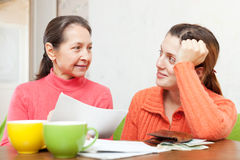 Mother helps adult daughter  to fills in bills Stock Photography