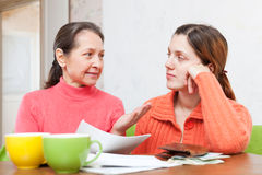 Mother helps adult daughter  to fills in bills Stock Images