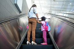 Mother helps alleviate fears on her daughter`s first ride on an escalator. A mother shares her daughter`s first time experiencing a ride up an escalator from stock image